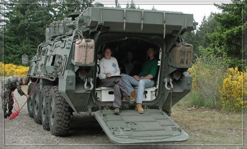Students sitting in military vehicle